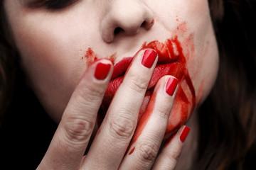 Female vampire licking blood off