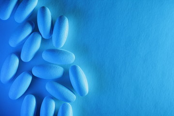 Medical pills on textured white background with blue lighting.