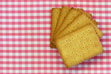 Classic crunchy biscuits on pink checkered cloth with copy space