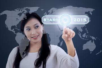 Hispanic woman pressing a start button