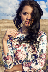 beautiful woman with dark hair posing In summer field
