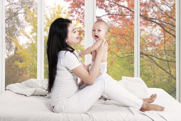 Joyful baby and mother in bedroom