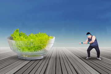 Person pulling a big bowl of salad