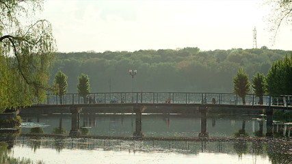 People enjoy sunset on bridge in Park