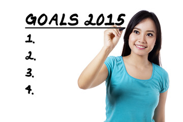 Smiling woman writes her goals