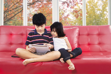 Two children with digital tablet on sofa