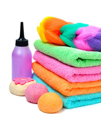Colorful stacked spa towels, bath bombs and shampoo bottle isola