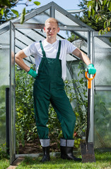 Gardener standing in front of greenhouse