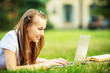 Smiling young student woman is using a laptop laying on grass
