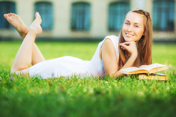 Young happy student woman with a book lying on a lawn in campus