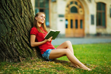 Young pretty student woman is sitting near the tree with a book