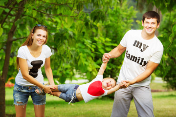 Happy young family is having fun in the summer park