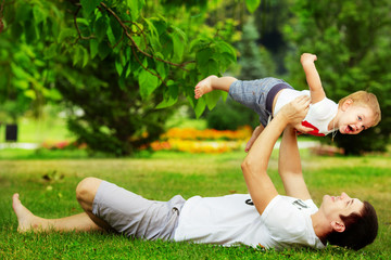 Happy father and son playing together in the green park