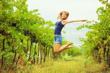 Happy woman in a vineyard in harvest season.