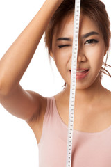 Asian slim girl wink her eye with measuring tape