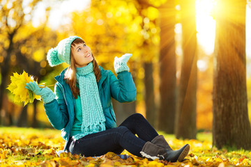 Beautiful happy young woman in the colourful autumn park.