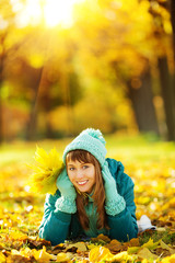 Beautiful happy young woman in the colorful autumn park.