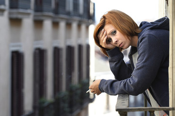 attractive woman suffering depression alone smoking at balcony