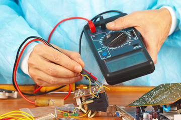 Serviceman checks electronic hardware with a multimeter