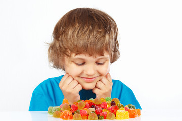 Boy with colored jelly candies on a white background