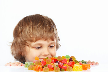 Little child with candies on a white background