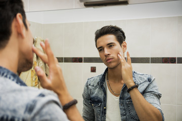 Handsome young man applying moisturizing cream on face