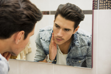 Handsome young man examining his face skin in bathroom mirror