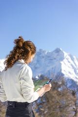 Ragazza guarda mappa con paesaggio invernale