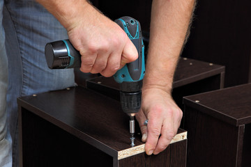 Hands carpenter with screwdriver, tighten screw in drawers of ch