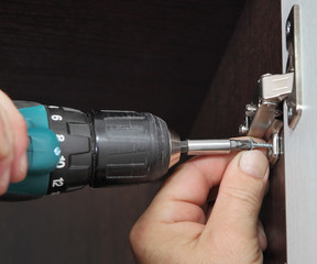 Assembling furniture, carpenter installs door hinges wardrobe, u