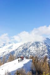 Gruppo di persone ciaspola in montagna