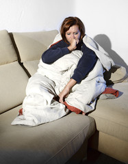 sick woman on couch wrapped in duvet and feeling miserable