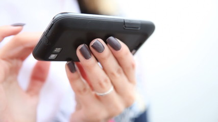 Hands of woman using cell phone smartphone outdoor