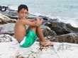 young child boy sitting on rocks ont he sea