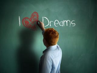 I love Dreams. Schoolboy writing on a chalkboard.