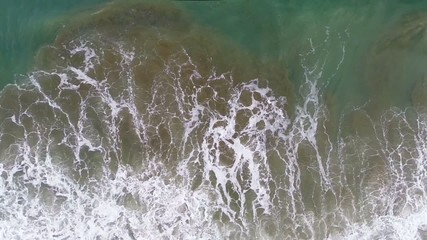 aerial view of waves clashing on the beach