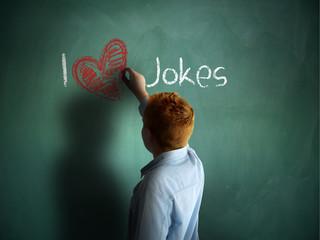 I love Jokes. Schoolboy writing on a chalkboard.