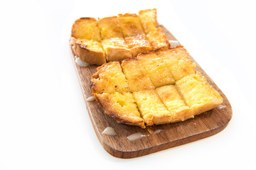 Bread toast and condensed milk on wooden plate