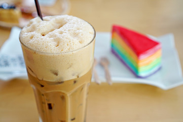 Iced coffee with rainbow crepe cake on a wooden table (Iced Capp