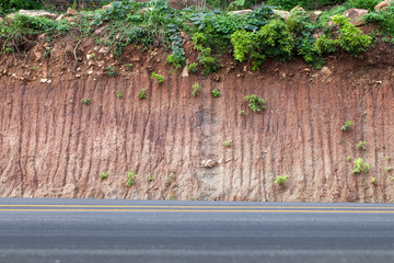Cross section of asphalt road with rock background.