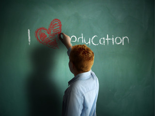 I love Education. Schoolboy writing on a chalkboard.