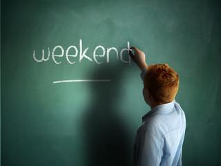 Weekend. Schoolboy writing on a chalkboard.