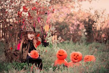 happy girl in halloween costume with jack pumpkin