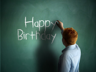 Happy Birthday. Schoolboy writing on a chalkboard.