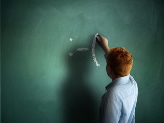 Sad. Schoolboy drawing an emoticon on a chalkboard