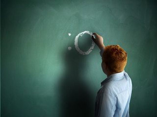 Surprised. Schoolboy drawing an emoticon on a chalkboard