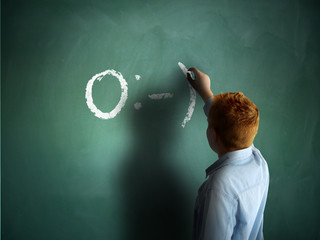 Angel. Schoolboy drawing an emoticon on a chalkboard