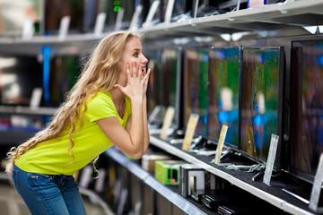 Красивая девушка выбирает телевизоры в магазине