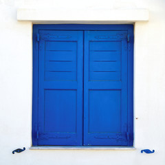 Greece, blue painted window shutters on white wall