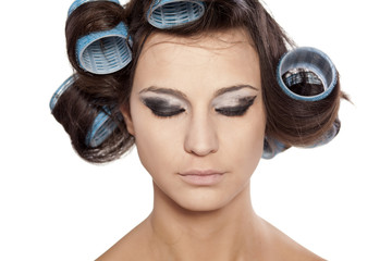 Funny woman with curlers and uncompleted bad makeup